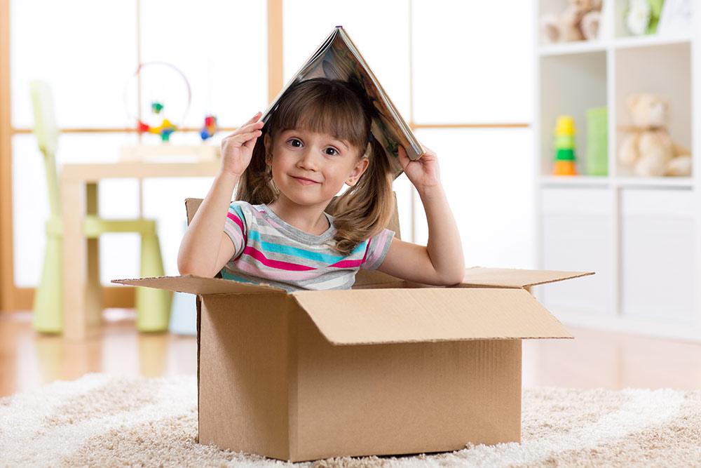 Criança feliz dentro da caixa com livro na cabeça