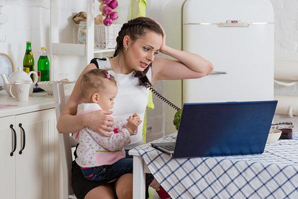 mãe exausta com bebê trabalhando