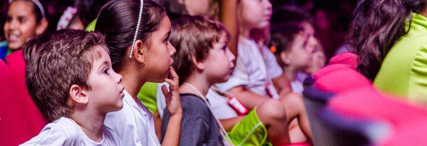 crianças assistindo teatro