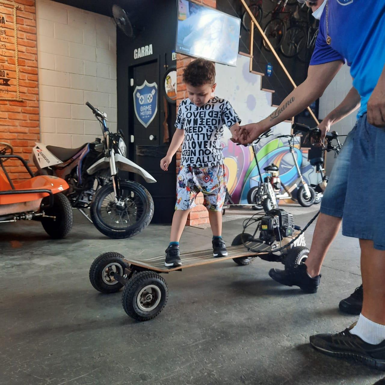 Niicholas aprendendo a andar de skate motorizado com os instrutores
